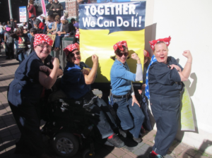 """At the top of the flyer, there is an photograph of four people wearing Rosie the Riveter costumes (red and white polka dotted bandanas and dark blue uniforms) in front of a """"Together, We Can Do It!"""" sign with their arms held in a muscular pose."""