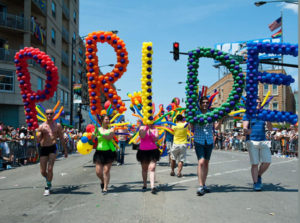 people marching in a pride parade with balloons gathered in the shapes of the letters p r i d e