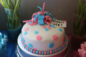 "cake with pink and blue decorations and a tag that says, ""Open me!"""