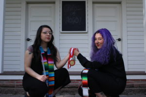Two graduates holding a medallion