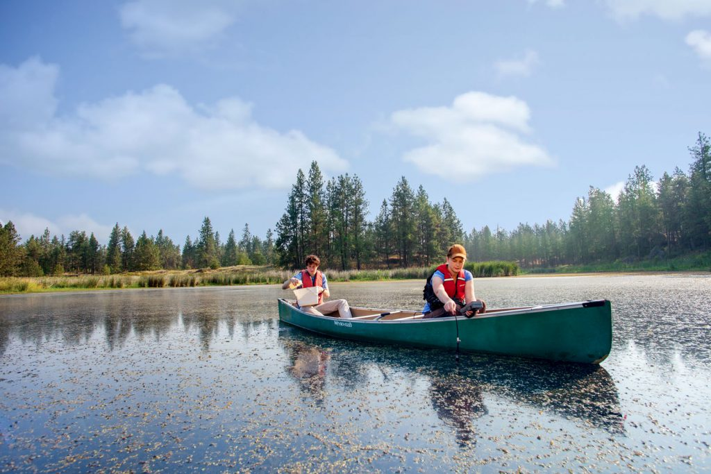 Students conduct research from a canoe