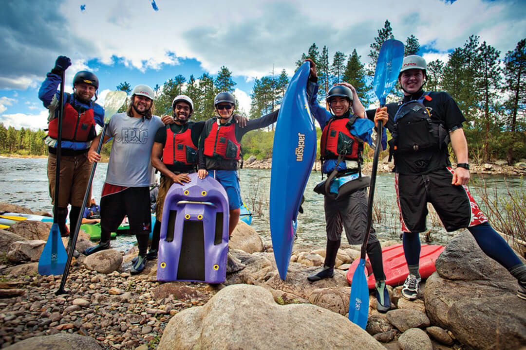 Photo: Six students posing with water sports gear on the shore of a river
