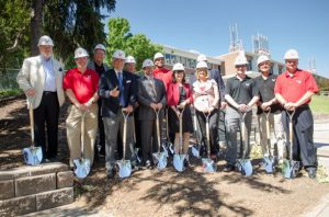 Group poses with shovels at the build site